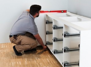 Plinth-adjusting system for installing kitchen cabinets